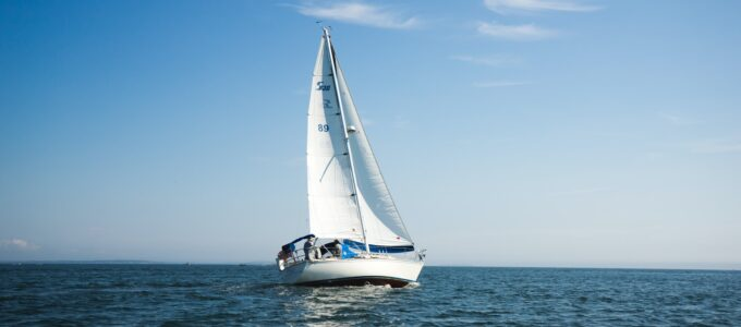 blue and white sailboat on ocean during daytime